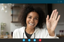 Head shot portrait screen view smiling African American woman greeting, waving hand, making video call to friends or relatives, looking at camera, using webcam and social media apps, engaged webinar
