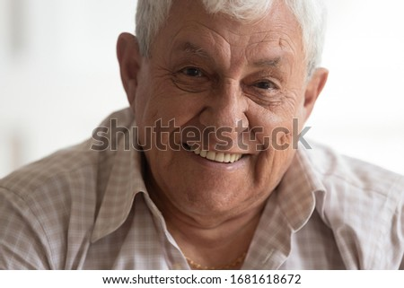 Head shot portrait senior retired man with healthy smile looking at camera close up, friendly grandfather posing for photo, grey haired male with wrinkles on face feeling positive, mature retiree