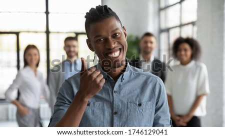 Head shot portrait smiling African American employee showing thumb up, standing with colleagues in modern office room, looking at camera, recommending corporate service, good career, human resources