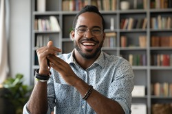 Head shot portrait smiling African American man wearing glasses making video call, looking at camera, confident positive young coach leading remote lesson, businessman participating online conference