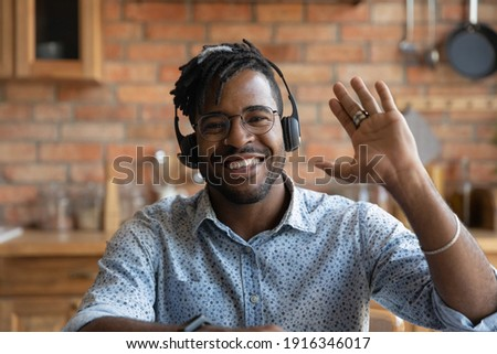 Head shot portrait smiling African American man wearing headphones and glasses greeting, waving hand at camera, friendly student or teacher in glasses involved in online conference, video call