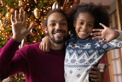 Head shot portrait smiling African American man with adorable daughter hugging, waving hands, making video call to relatives with Christmas tree on background, congratulating with winter holiday