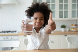 Head shot portrait smiling African American pretty little girl showing thumb up, holding glass of pure clean mineral water, recommending healthy lifestyle, everyday habit, refreshment concept