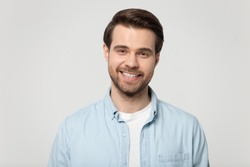 Head shot portrait smiling attractive confident millennial man wearing blue shirt posing on grey studio background, guy with bristle having white toothy smile advertise dental services or procedure