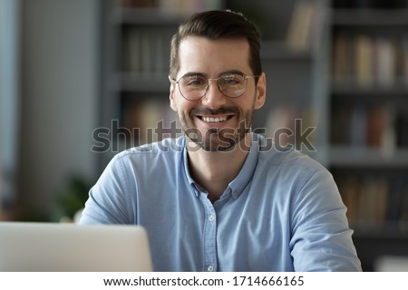 Head shot portrait smiling businessman student worker wearing glasses looking at camera, happy satisfied young man sitting at work desk with laptop, posing for photo in modern cabinet