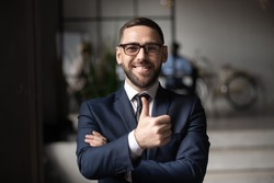 Head shot portrait smiling businessman wearing glasses showing thumbs up, looking at camera, happy employee intern satisfied successful work result, good news, client recommending service