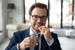 Head shot portrait smiling businessman wearing glasses taking meds, medication pills in office, holding glass of water, looking at camera, happy man employee drinking daily vitamins, supplements