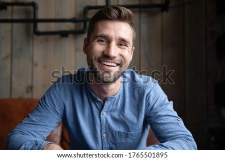 Head shot portrait smiling Caucasian man sitting indoors having pleasant web cam videoconference on-line chat by work or informal speak use pc. Job interview, tutoring video call, modern tech concept