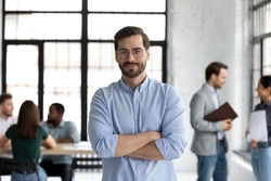Head shot portrait smiling confident businessman wearing glasses standing in modern office room with arms crossed, diverse colleagues on background, executive boss startup founder looking at camera