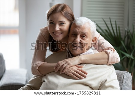 Head shot portrait smiling grownup daughter hugging older father from back, looking at camera, two generations concept, beautiful young woman embracing mature man, posing for photo together
