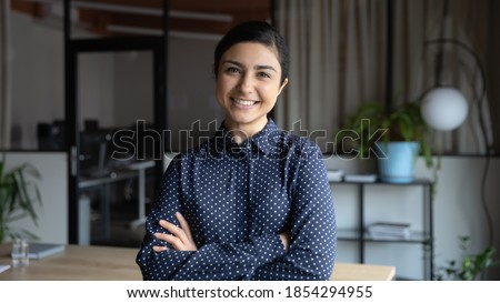 Head shot portrait smiling Indian businesswoman standing in modern office with arms crossed, confident successful young female employee intern looking at camera, posing for corporate photo Foto stock ©