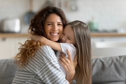 Head shot portrait smiling loving mother hugging adorable little daughter, looking at camera, caring happy mum and cute preschool girl enjoying tender moment, sitting on cozy couch at home