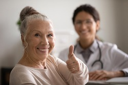 Head shot portrait smiling mature female patient showing thumb up, female therapist and senior man sitting in doctor office, old client satisfied by health insurance or healthcare service concept