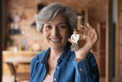 Head shot portrait smiling mature woman holding key from new home, own apartment, looking at camera, excited mature female owner moving into new house, satisfied client customer purchase real estate