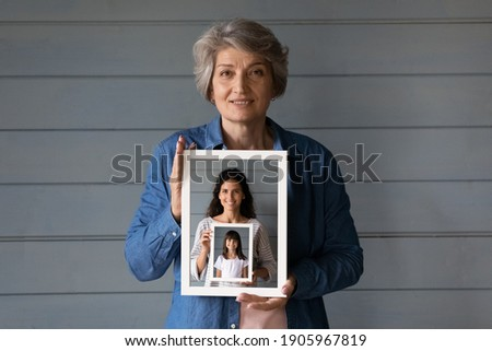 Head shot portrait smiling mature woman holding photo frame of grownup daughter and little granddaughter in row, standing on grey wooden wall background isolated, three generations of women concept
