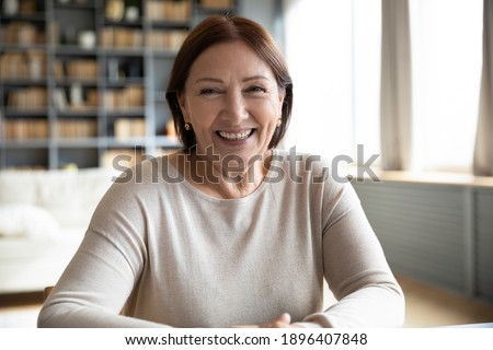 Head shot portrait smiling mature woman making video call, grandmother chatting with relatives, using webcam, happy middle aged blogger recording vlog, teacher holding online lesson, distance lecture
