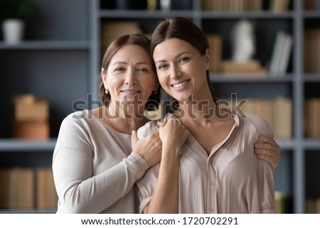 Head shot portrait smiling middle aged mother with adult grown up daughter looking at camera, happy young woman with older mum hugging, standing in living room at home and posing for family photo