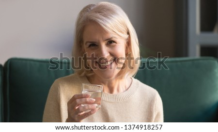 Head shot portrait smiling middle aged woman holding glass of fresh pure water in hand, happy grey haired mature female looking at camera, health care concept, healthy lifestyle, horizontal banner