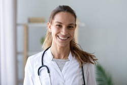 Head shot portrait smiling mixed race female doctor nurse in white uniform with stethoscope on neck, happy therapist physician practitioner woman looking at camera, healthcare concept