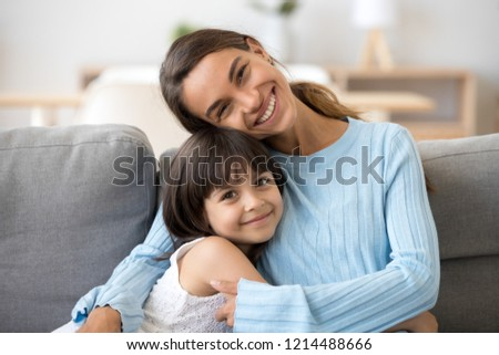 Head shot portrait smiling mixed race mother embrace little daughter sitting together on sofa posing looking at camera at home happy motherhood love and tenderness relationships between kid and mom