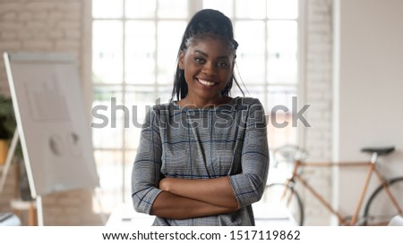 Head shot portrait smiling mixed race young businesswoman looking at camera. Successful confident african american female team leader, company owner, trainer coach mentor posing at modern workplace.