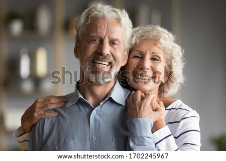 Head shot portrait smiling older man and woman hugging, looking at camera, mature married couple posing for photo at home, happy caring senior wife embracing hugging husband from back