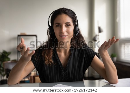 head shot portrait smiling woman in headphones speaking at camera, teacher recording webinar, businesswoman consulting client online, video call, involved in virtual meeting, blogger shooting vlog