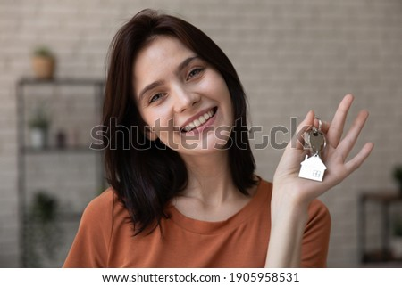 Head shot portrait smiling woman tenant showing keys to new apartment, looking at camera, happy female customer excited by purchasing new house, moving to first dwelling, mortgage or rent concept Stockfoto ©