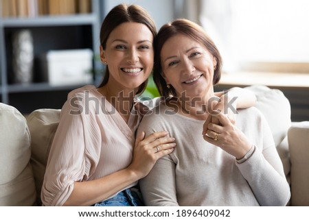 Head shot portrait smiling young woman hugging mature mother, sitting on couch together, happy middle aged mum and adult grownup daughter looking at camera, posing for family photo at home