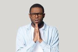 Head shot portrait upset African American man in glasses joining hands in prayer gesture with hope isolated on grey studio background, unhappy young male with closed eyes asking help and support