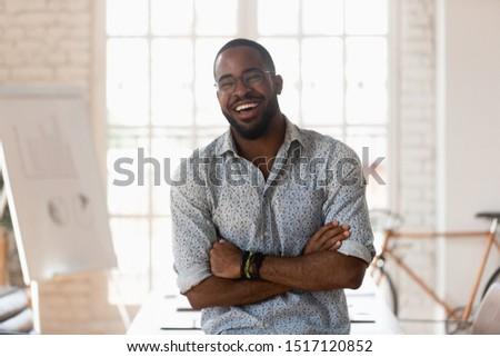 Head shot portrait young joyful mixed race male manager having fun, laughing, enjoying break time at modern creative office. Overjoyed multiracial businessman in glasses joking, posing at workplace.