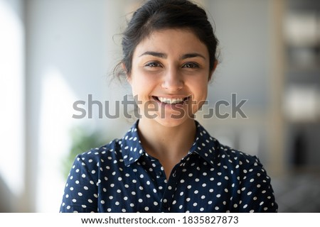 Head shot positive 25s Indian female smiling looking at camera. Successful business woman, career advance of worker, happy student or intern new employee portrait, video call profile picture concept