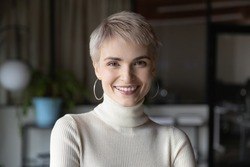 Head shot profile portrait of young happy short haired blonde businesswoman in modern office. Smiling 30s female manager, talented corporate employee, confident saleswoman looking at camera.