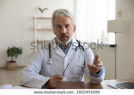 Head shot serious mature doctor wearing white uniform coat with stethoscope speaking, looking at camera, gesturing, senior therapist practitioner gp consulting patient online, making video call