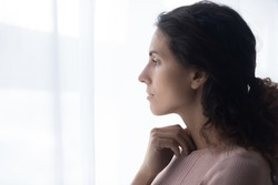 Head shot side view thoughtful young caucasian woman standing near window, looking in distance, thinking of difficult personal problems solutions, felling melancholic alone indoors, copy space.