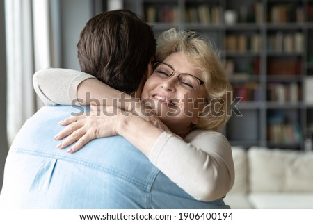 Head shot sincere loving middle aged older woman in eyeglasses cuddling affectionate grown son, meeting on weekend at parent's house, showing care and devotion, different generations family relations.