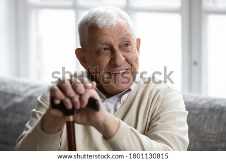 Head shot smiling old disabled man holding hands on wooden stick, resting on cozy couch in living room. Happy elderly senior grandmother recollecting good memories, enjoying relaxation time indoors.