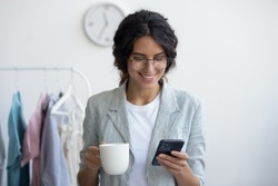 Head shot smiling young businesswoman holding cup of tea coffee, consulting clients online using mobile application. Happy millennial creative designer stylist enjoying pause break time in office.