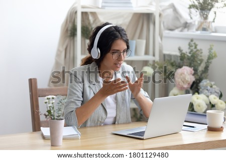 Head shot smiling young creative businesswoman in glasses wearing wireless headphones, enjoying video call conversation with partners or giving professional consultation to client online in showroom.