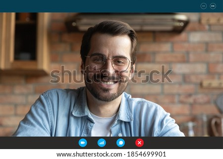 Head shot smiling young man in eyeglasses holding video call meeting with colleagues from home, skilled male teacher giving educational distant remote class to students, computer app screen view.