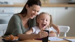 Head shot smiling young mother showing funny cartoons to overjoyed little adorable girl on smartphone. Happy 30s woman recording family video with laughing small preschool daughter on mobile phone.