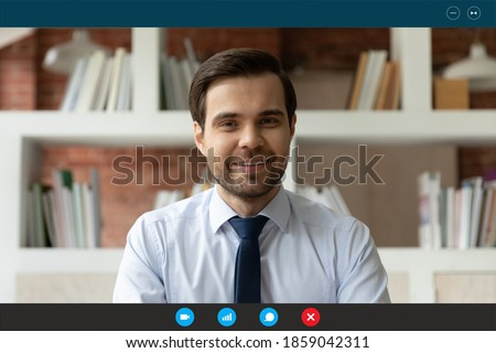 Head shot smiling young successful businessman in formal shirt and tie holding video call online meeting with colleagues or partners, discussing working issues, computer application display view.