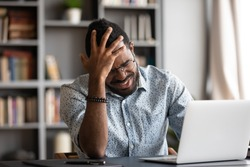 Head shot stressed young african american man touching forehead, suffering from terrible headache, working on computer at home office. Frustrated confused biracial guy having painful feelings in head.