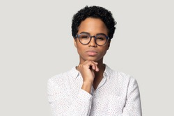 Head shot studio portrait isolated on gray background frowned serious confident African woman wearing glasses puts chin on fist staring at camera suspect something looking distrustful, sceptic concept