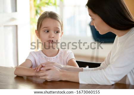 Head shot unhappy small child girl sitting at table with worrying mother, sharing school problems. Compassionate caring attentive mommy having trustful conversation with unhappy offended daughter.