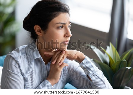 Head shot unhappy thoughtful Indian woman thinking about psychological problems close up, looking away, feeling depressed, sitting on couch alone, sad upset young female worried about break up