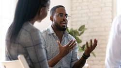 Head shot young african american male psychologist meeting patients at group therapy. Serious mixed race counselor giving advices to employees. Confident business coach training staff at office.