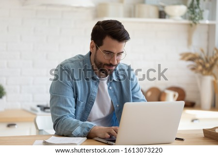 Head shot young businessman sitting at table with computer, working remotely, writing email or reading news. Young man attending distant educational courses, planning job or communicating online.