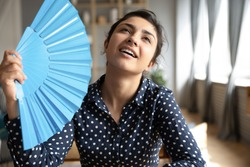 Head shot young indian woman using blue paper fan, feeling hot relieved indoors. Sweaty millennial hindu girl teenage cooling herself, breathing fresh air, spending time at home without conditioner.
