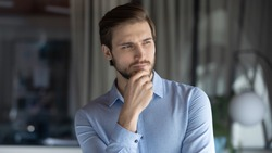 Head shot young pensive businessman touching chin, looking in distance, thinking of professional challenges alone in office. Thoughtful millennial manager finding project problem solution indoors.